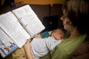 Junger Vater mit Baby auf dem Bauch am Lernen