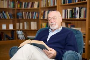 älterer Mann liest ein Buch und bildet sich weiter