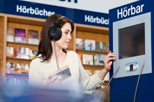 Frau hört Hörbuch in Bibliothek