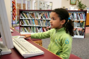 Kind in Bibliothek am Computer